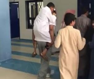 شاهد.. معلم يحمل طالباً من ذوي الاحتياجات الخاصة ويصعد به الدرج !