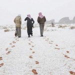 Saudi men walk as their footprints are seen after a snowstorm in Alkan village, west of Saudi Arabia