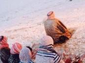 بالصورة …أب وأبنائه يؤدون الصلاة تحت تساقط الثلوج بالقريات
