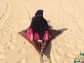 """شاهد… سعودي يُزلج """"زوجته"""" المُسنة على رمال الصحراء"""