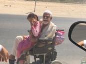 """بابتسامة وحب … ابن الأحساء """"العباد"""" يرافق ابنته للمدرسة يوميًا على """"كرسي متحرك"""" !!"""