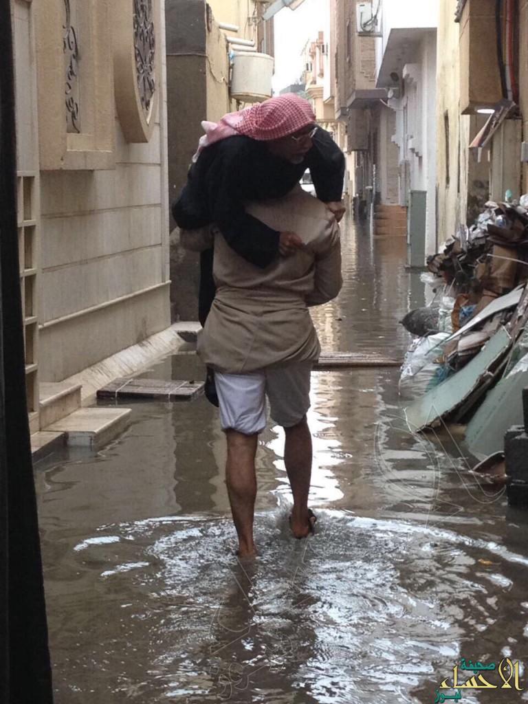 """بالصور… مياه الأمطار تختبر """"بر"""" أحد الأبناء بوالده!!"""